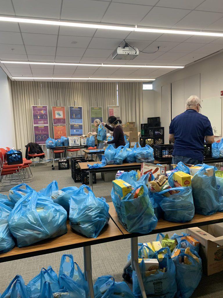 Three volunteers bagging food at an APAH grocery distribution