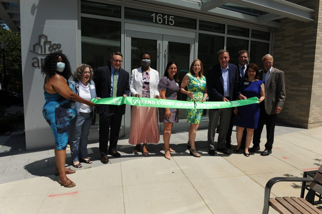 APAH leaders join local, state and federal government representatives to cut the grand opening ribbon at Queens Court in June, 2021